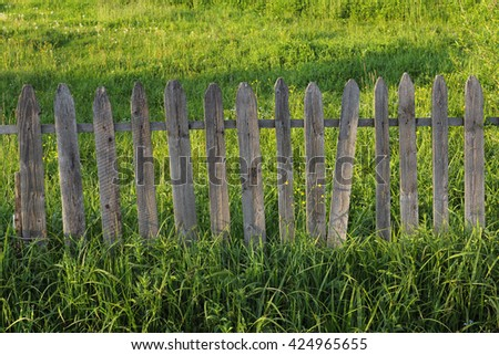 old wooden fence in green field with lush grass
