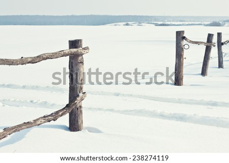 Old wooden fence in snow - stock photo