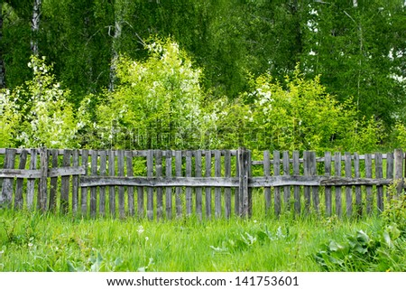 Old wooden fence in village with orchard behind - stock photo