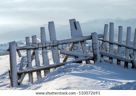 Old wooden fence on a hill in the winter under the snow.