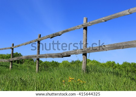 old wooden fence on meadow with green grass