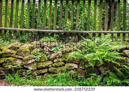 Old wooden fence on the rocks - stock photo
