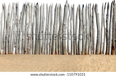 old wooden fence on the sand isolated on the white background - stock photo