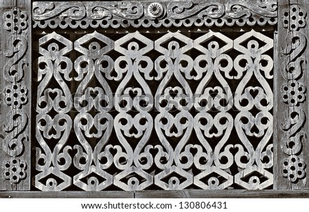 Old wooden fence with an openwork carving. - stock photo