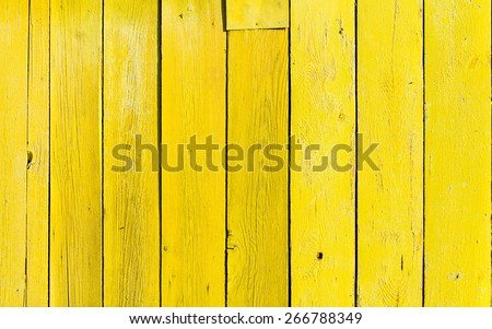 old wooden fence with yellow paint - stock photo
