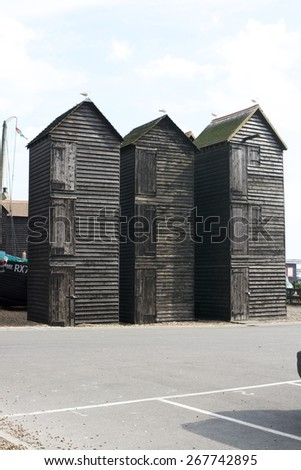 Old Wooden fisherman huts on the shingle beach at Hastings old town, East Sussex, England - stock photo