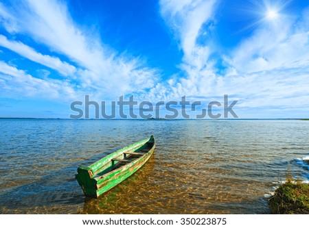 Old wooden fishing boat on summer lake bank and sunshine in blue sky (Svityaz, Ukraine) - stock photo