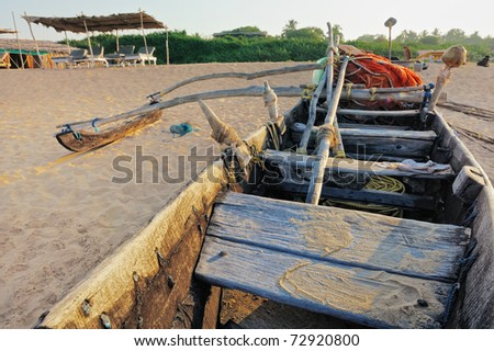 Old wooden fishing boat on the sandy beach - stock photo