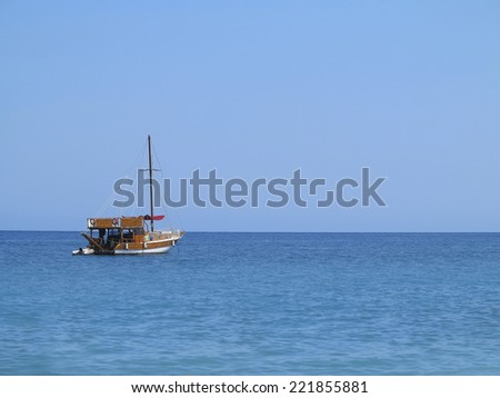 Old wooden fishing boat trawler over calm blue sea and sky - stock photo