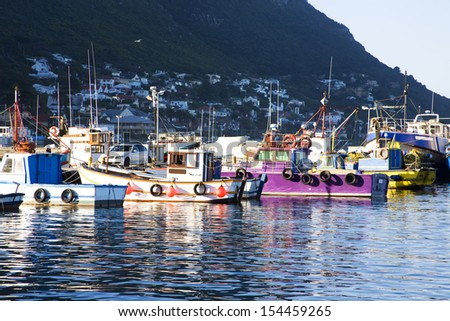 Old wooden fishing boats moored in Kalk Bay Harbour, Cape Town, South Africa - stock photo