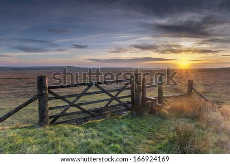 Old wooden five bar field gate and stile on windswept moorland at Bodmin Moor in Cornwall - stock photo