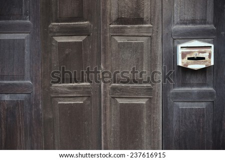 old wooden folding door with old mailbox
