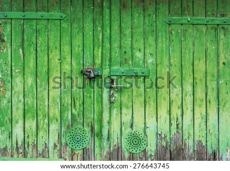Old wooden garage gate with faded paint - stock photo