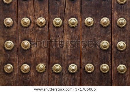 Old wooden gate fixed with large brass rivets in Cordoba, Andalusia, Spain.  - stock photo