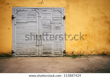 Old wooden gate in grungy yellow wall - stock photo