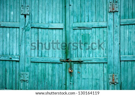 Old wooden gate with faded paint - stock photo