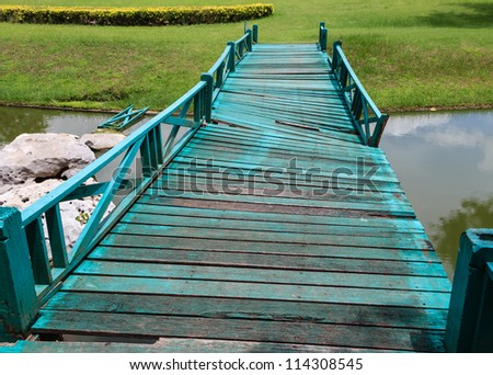 Old Wooden Green Bridge Collapses Down the Stream. - stock photo
