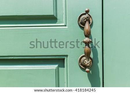 Old wooden green door with antique door handle - stock photo