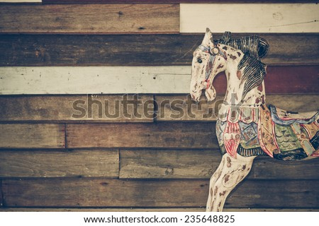 old wooden horse with wood plank wall background - stock photo