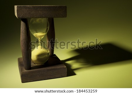 Old wooden hourglass with shadow in yellow light - stock photo
