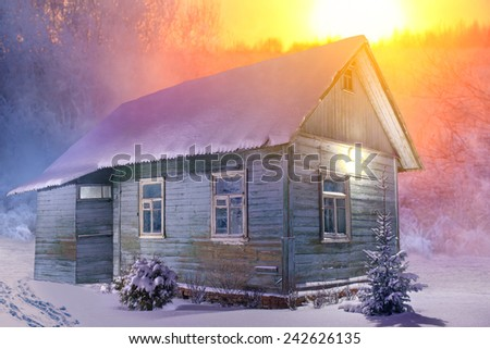 Old wooden house in forest at cold winter season. Red sunset light. - stock photo