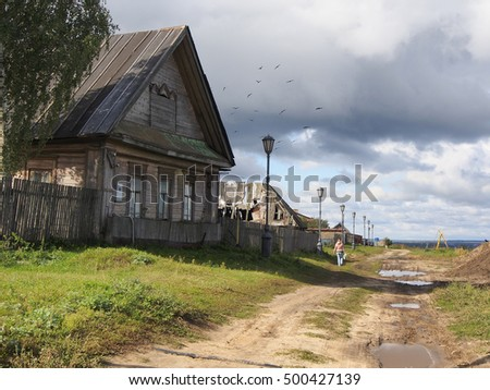 Old wooden house in russian village, road, puddles