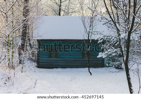 Old wooden house in snowy winter forest