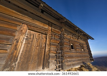 old wooden house on a background of blue sky, the entrance to the house, window, door, texture - stock photo