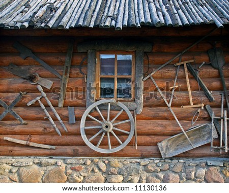 Old wooden house with tolls, window and wheel - stock photo