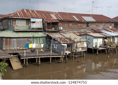 Old wooden houses beside the Chao Phraya River. Bangkok, Thailand. - stock photo