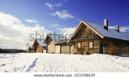Old wooden houses in winter, Minsk region, Ozertso village, Belarus - stock photo