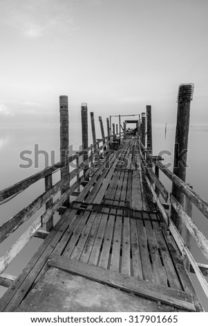 Old wooden jetty in black and white - stock photo