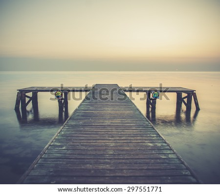 Old wooden jetty, pier on the sea. Raining from dramatic sky with dark, heavy clouds. Sopot - stock photo
