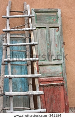 Old wooden ladder and doors against a wall in  a courtyard in Santa Fe, NM. - stock photo