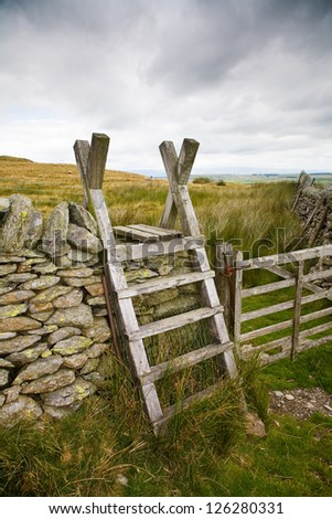 Old wooden ladder stile set against the beautiful Cumbrian countryside. - stock photo