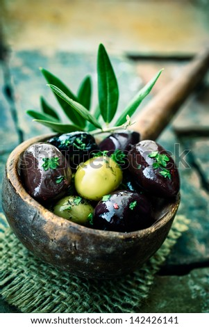 Old wooden ladle or large spoon filled with seasoned black and green olives decorated with an olive-tree branch - stock photo