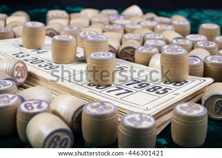 Old wooden lotto barrels and cards on green velvet (soft focus). - stock photo