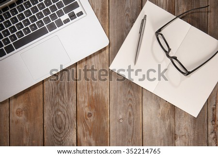 Old wooden office table with planner, pen, laptop and glasses. View from above with copy space. - stock photo