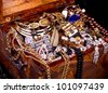 Old wooden open chest with golden jewelry - stock photo