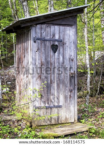 old wooden outhouse at a forest - stock photo