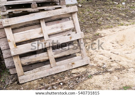Old wooden pallets are piled in heap on ground