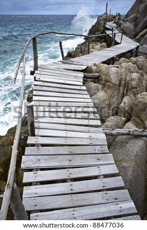 Old wooden pathway over the sea - stock photo