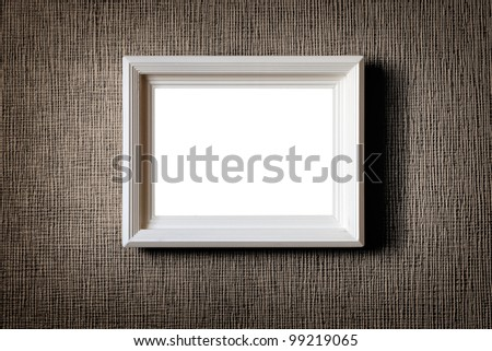 Old wooden picture frame on wall background - stock photo