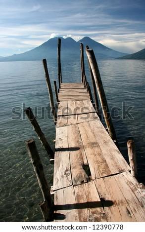 Old wooden pier jutts out into Lake Atitlan, volcanoes in background. Atitlan. Guatemala - stock photo