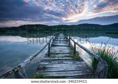 Old wooden pier on a lake at sunrise - stock photo