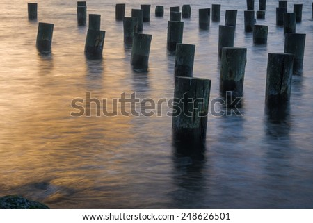 Old wooden pillars sitting in the East River of New York City at sunset - stock photo