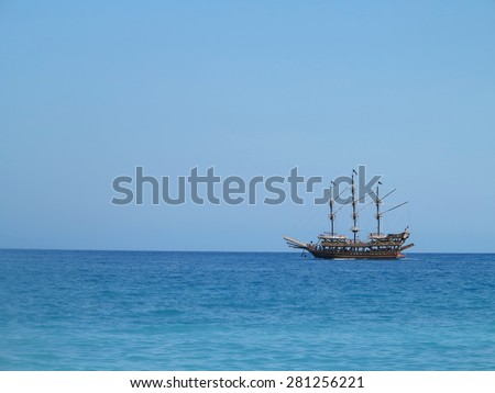 Old wooden pirate old ship in blue sea - stock photo