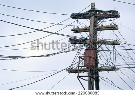 Old wooden pole with power line and telephone line cables, old wired communications - stock photo