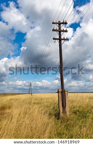 Old wooden poles - the line of electricity transmissions - in the field - stock photo