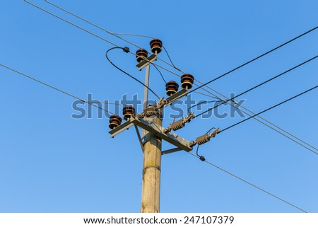 Old wooden power transmission pole with wires on a sky background - stock photo